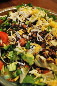 A close up image of Taco Salad in a glass serving bowl.