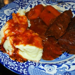 A plate of barbecue braised short ribs with mashed potatoes and carrots.