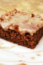 A slice of pumpkin gingerbread cake on a white plate.