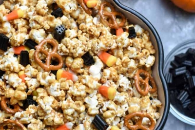 A bowl of caramel corn with mini pumpkins and candy on the side.