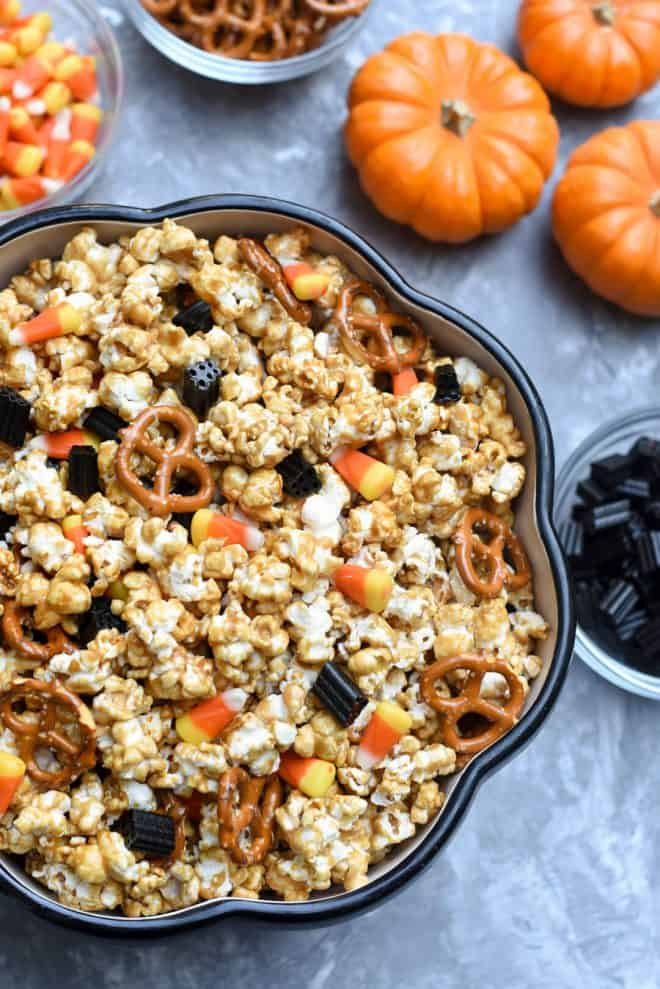 A big bowl of Caramel Corn with small pumpkins and bowls of treats around it.