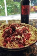A plate of spaghetti and meatballs with a bottle of wine.
