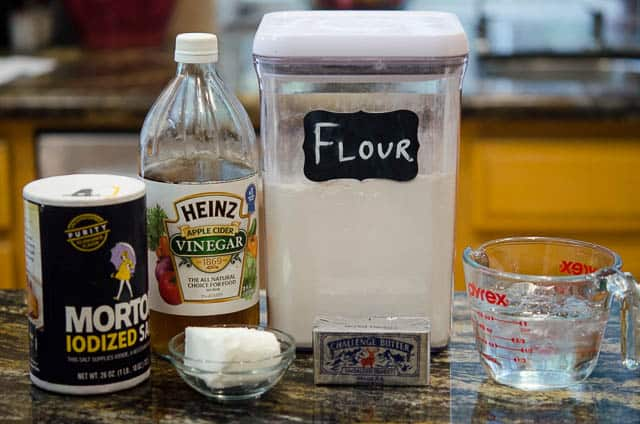 All-purpose flour, unsalted butter, shortening, cider vinegar, ice water, and salt on a kitchen counter.