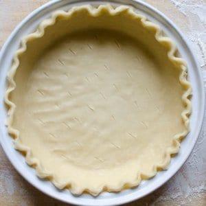A pie dish with raw pie crust dough inside.