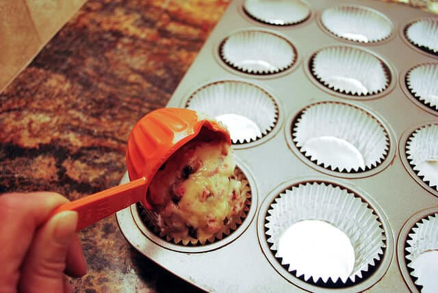 The orange measuring cup is scooping muffin batter to fill the muffin cups.