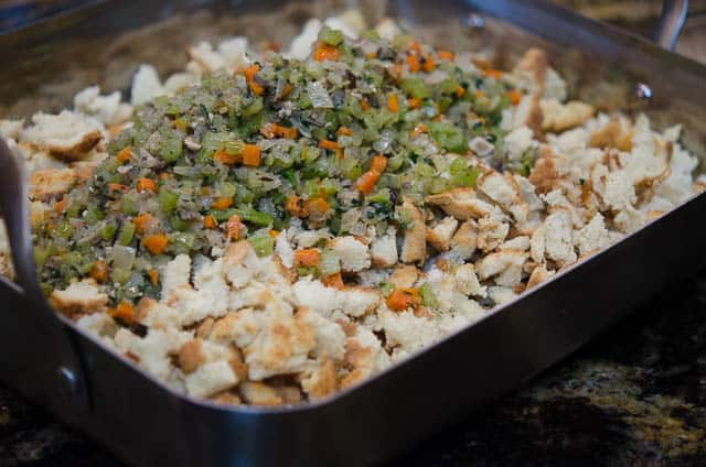 The veggies are poured over the top of the toasted bread for the Crock Pot Stuffing in a large roasting pan.