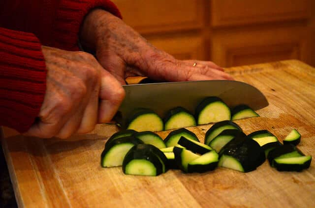 Bonnie cutting up zucchini on a cutting board.