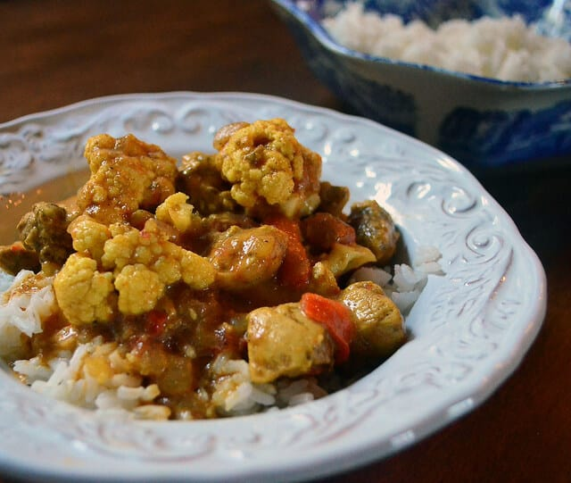 A dish of coconut curry chicken served on white rice.