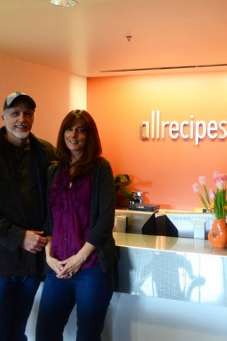 A man and a woman standing in a room in front of an allrecipes.com sign.