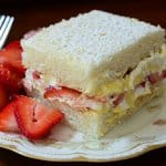 A slice of cake with a side of strawberries.