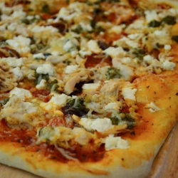 A close up of chicken pesto pizza.