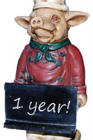 A ceramic pig dressed as a chef holding a chalkboard sign that says 1 year!