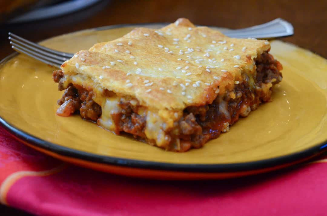 A made from scratch filling is topped with cheese and baked between layers of crescent roll dough. These Sloppy Joe Squares are a fun, delicious meal!