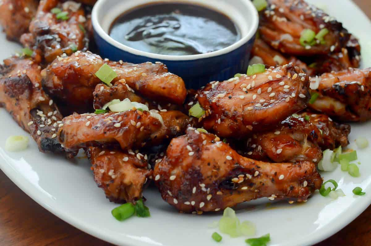 The finished Sticky Baked Asian Chicken wings served on a plate with a side of extra sauce.