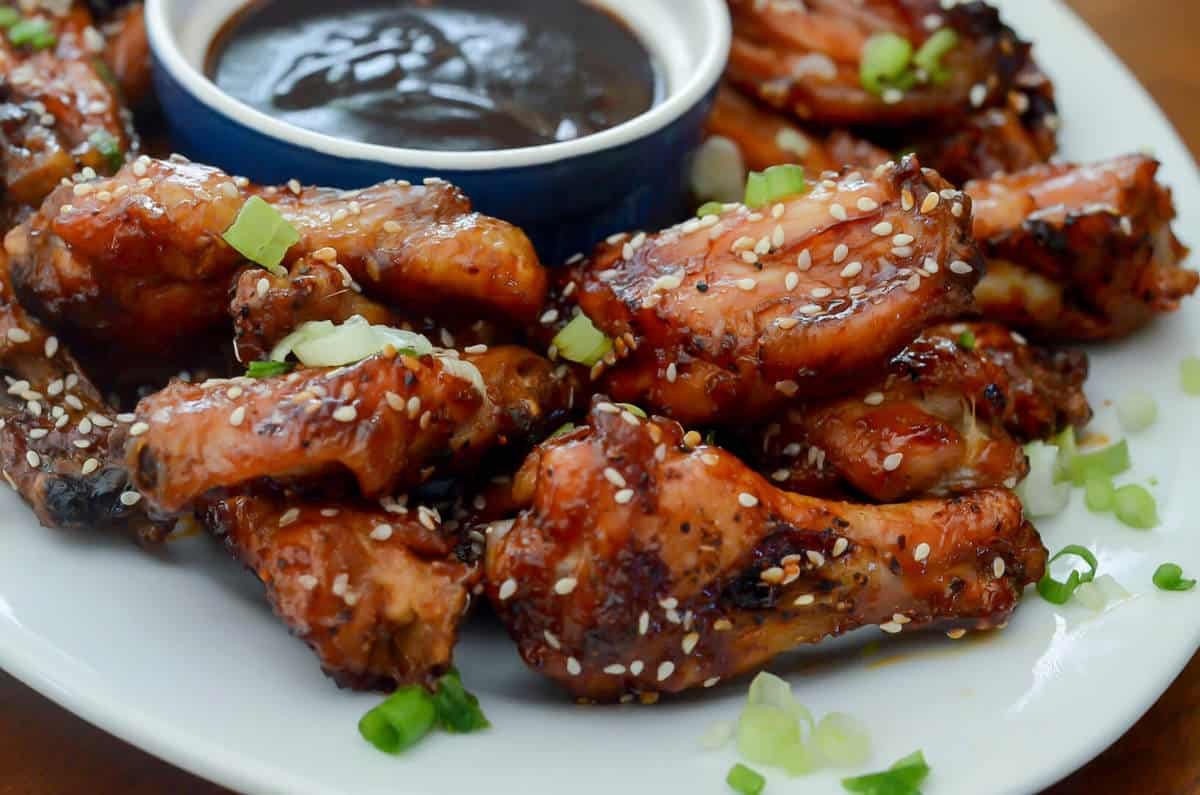 A white tray filled with Asian Chicken Wings with a small bowl of sauce.
