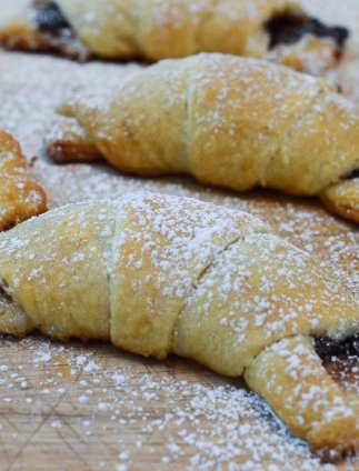 A close up of crescent rolls stuffed with chocolate a dusted with powdered sugar.