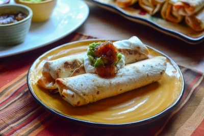 Two taquitos on a plate topped with sour cream, guacamole, and salsa.