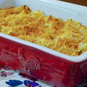 A red casserole dish full of cheesy hash browns with a browned topping.