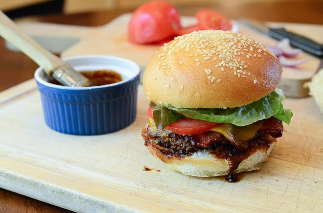 Assembling the Stout & Sriracha Barbecue Bacon Burgers on a wood cutting board.