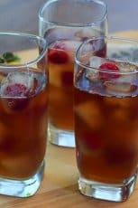 Three glasses of iced tea and lemonade with ice cubes and raspberries.