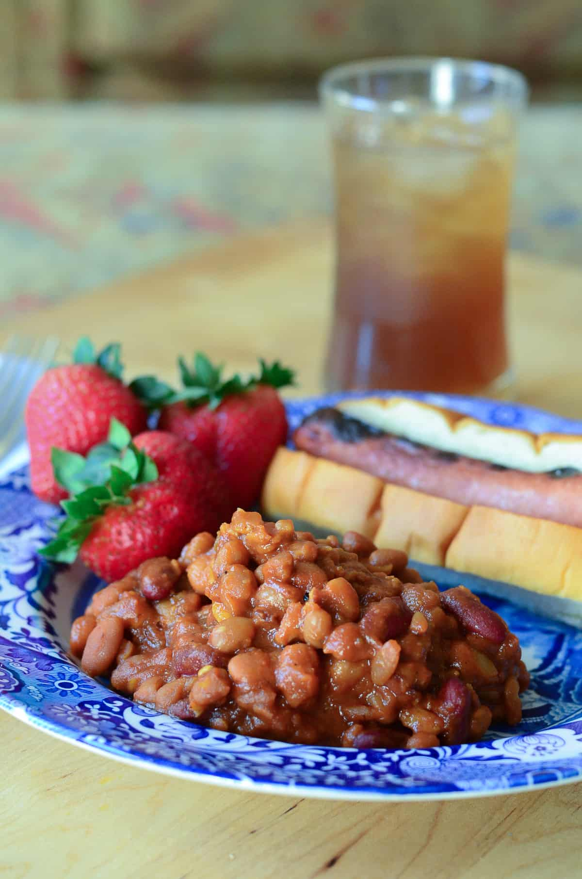A serving of Spicy Baked Beans on a blue plate with a hot dog and strawberries.