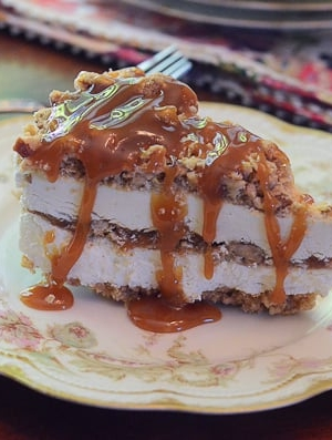 A piece of ice cream cake drizzled with caramel sauce on a plate.