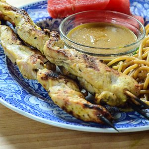 Skewers of grilled chicken on a plate with a small bowl of peanut sauce.