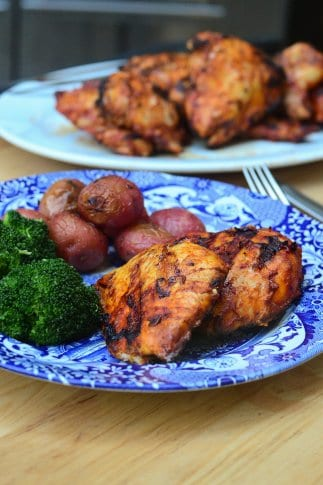 Grilled paprika chicken on a blue plate with broccoli and potatoes.
