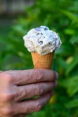 A hand holding an ice cream cone.