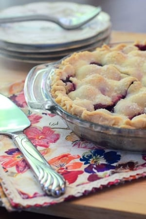 A cherry pie on a colorful cloth.