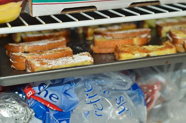 A baking sheet full of Nutella Stuffed French Toast Sticks inside a freezer.