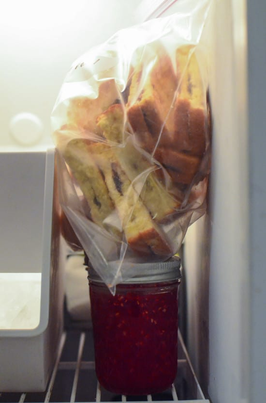 A bag of Nutella Stuffed French Toast Sticks sitting on top of jars of jam inside a freezer.