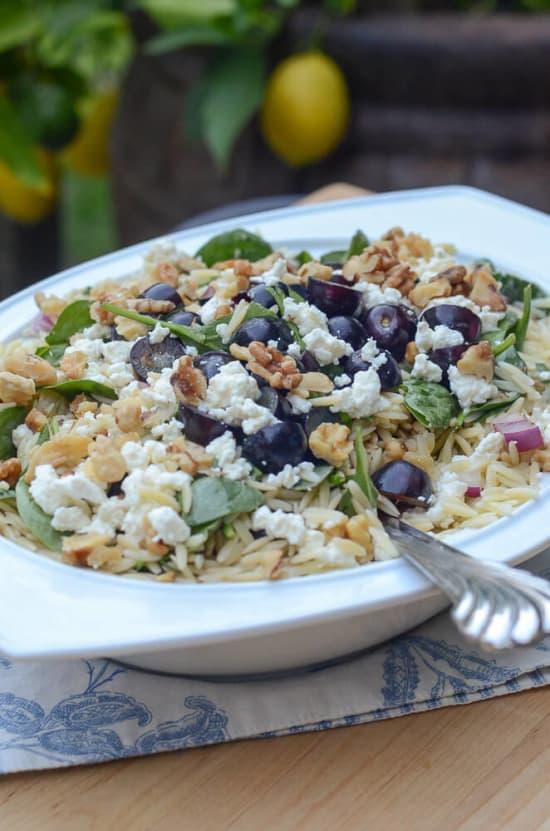 A serving bowl full of Orzo Grape Feta Salad.