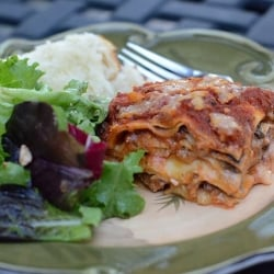 Lasagna and salad on a plate.