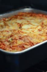 Lasagna in a metal pan in the oven.