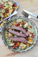 Panzanella salad with strips of medium rare steak on top.