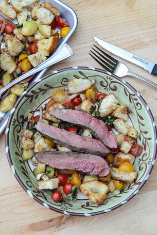 Panzanella salad with strips of medium rare steak on top.
