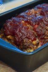 Glazed meatloaf in a loaf pan.