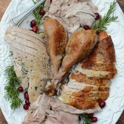 Slices of turkey and drumsticks on a serving platter.
