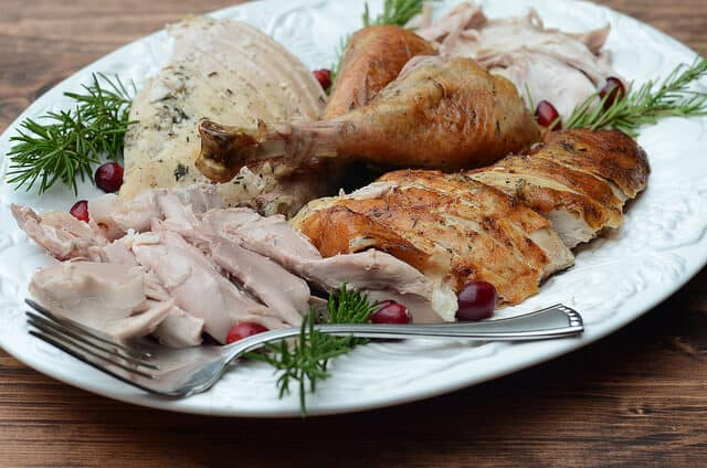A white tray filled with sliced roasted turkey.