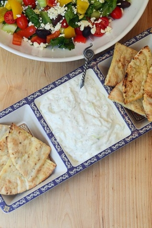 Tzatziki and toasted pitas in a serving dish.