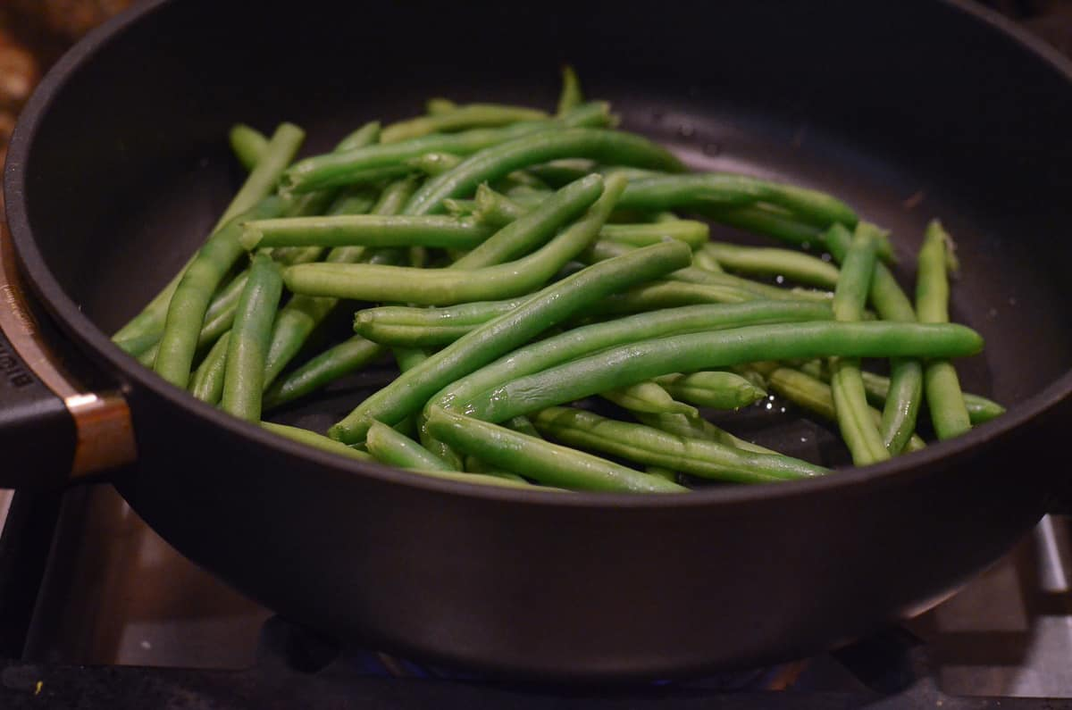 The partially cooked green beans in a skillet.