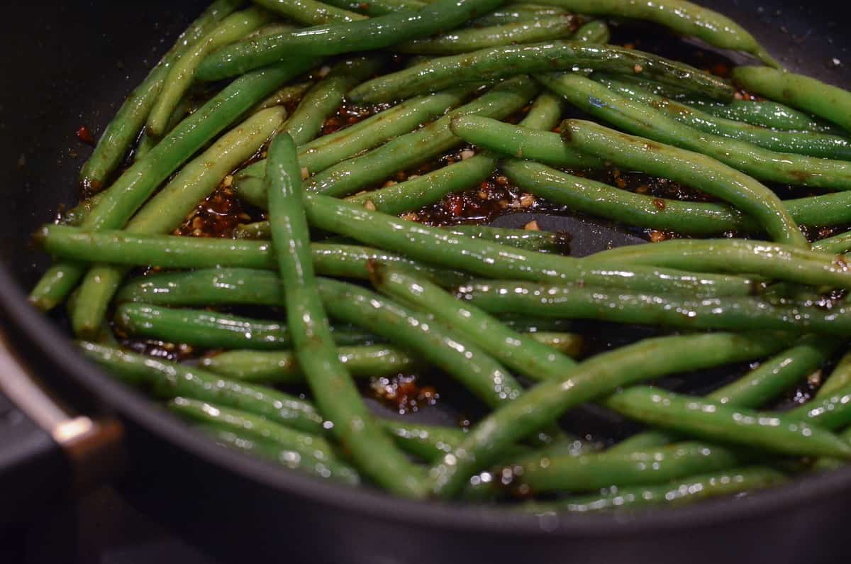 The green beans are sauteed with the chili garlic sauce in the skillet.