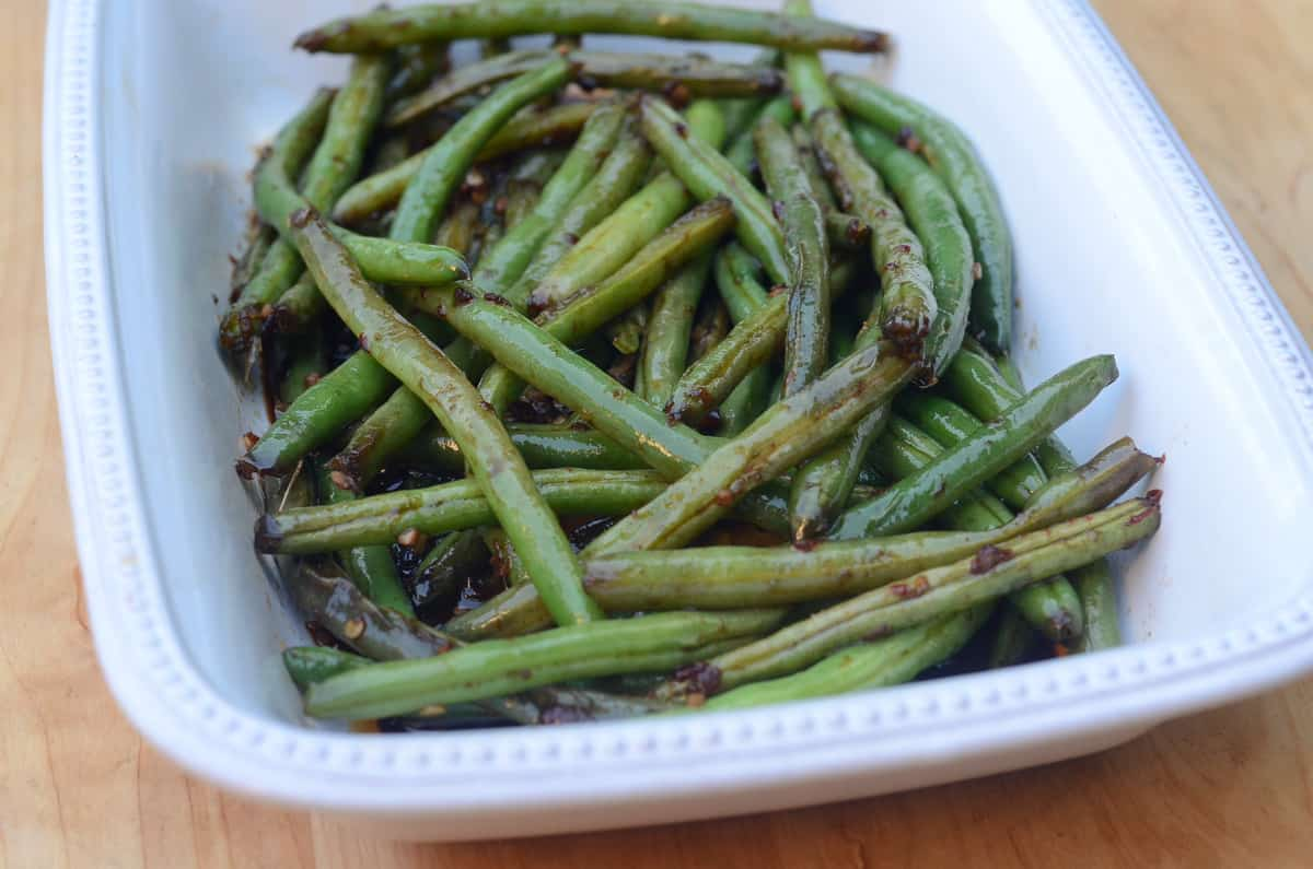 The Asian Style Green Beans are transferred to a while serving dish.