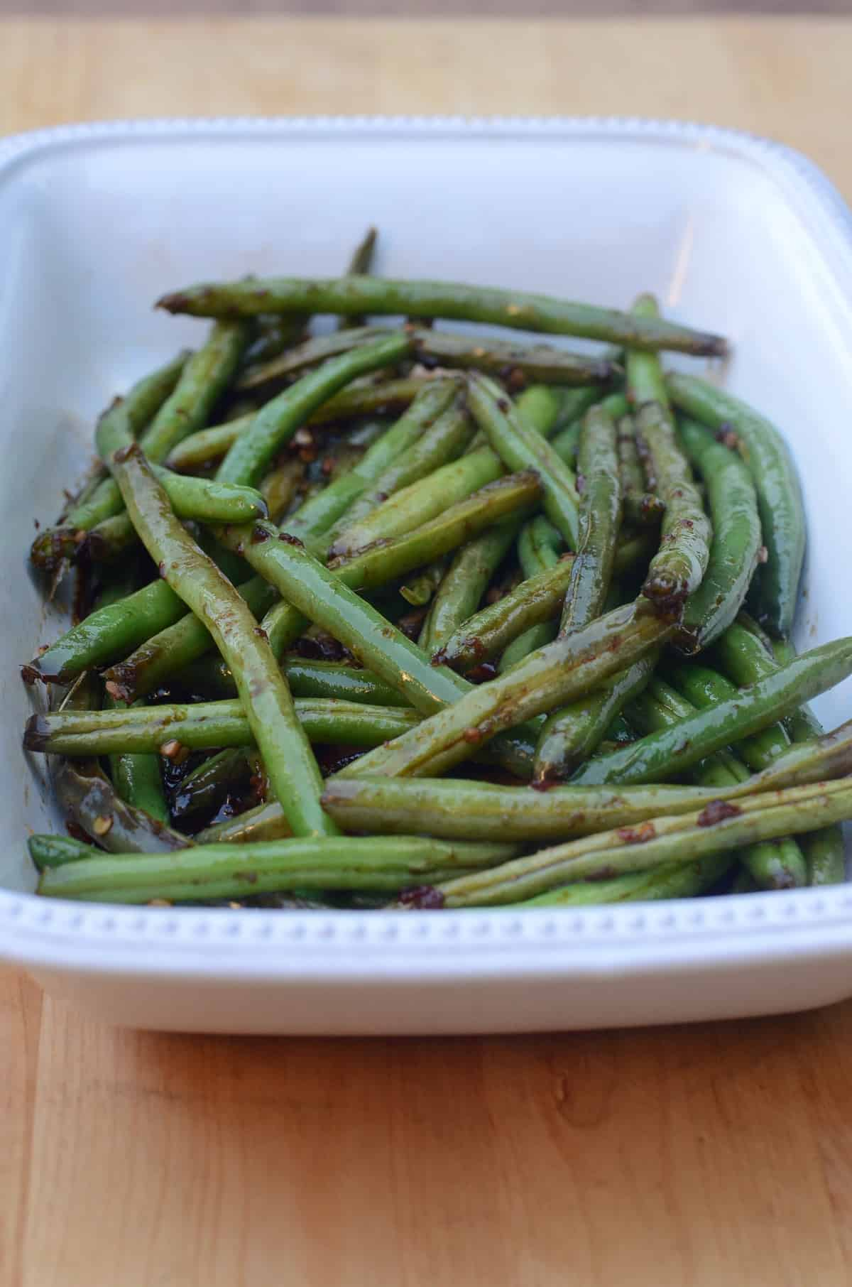 Sweet and Spicy Asian Style Green Beans in a white serving dish.