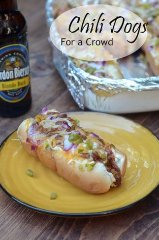 A yellow plate with a chili dog next to a beer.