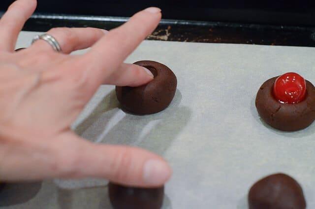 A finger presses into a ball of dough.