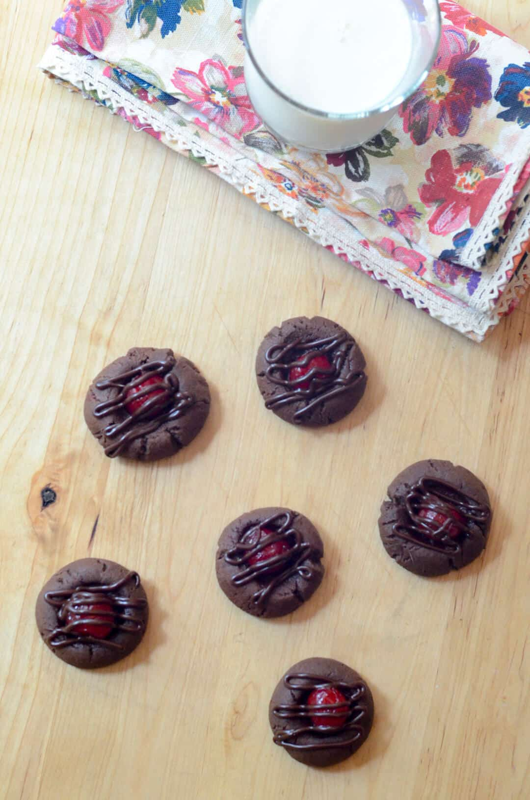 Chocolate cookies topped with cherries and melted chocolate on a wooden board.