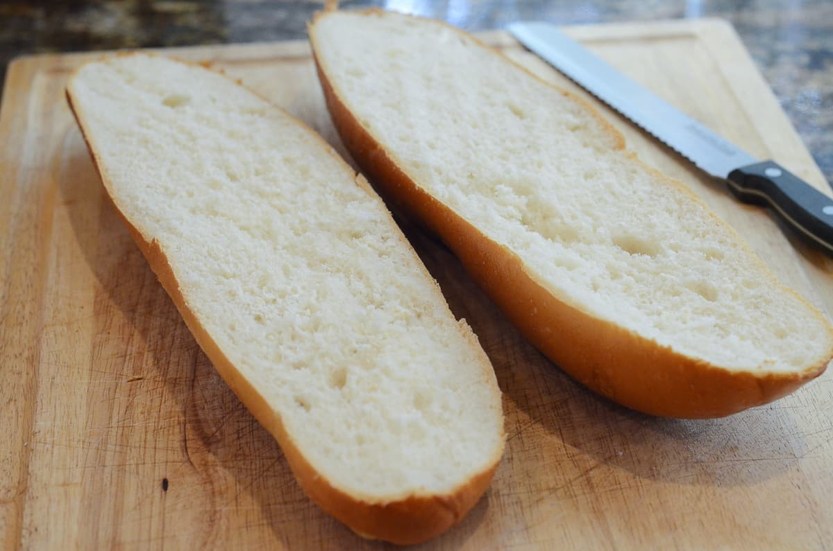 A loaf of French bread sliced in half on a cutting board.