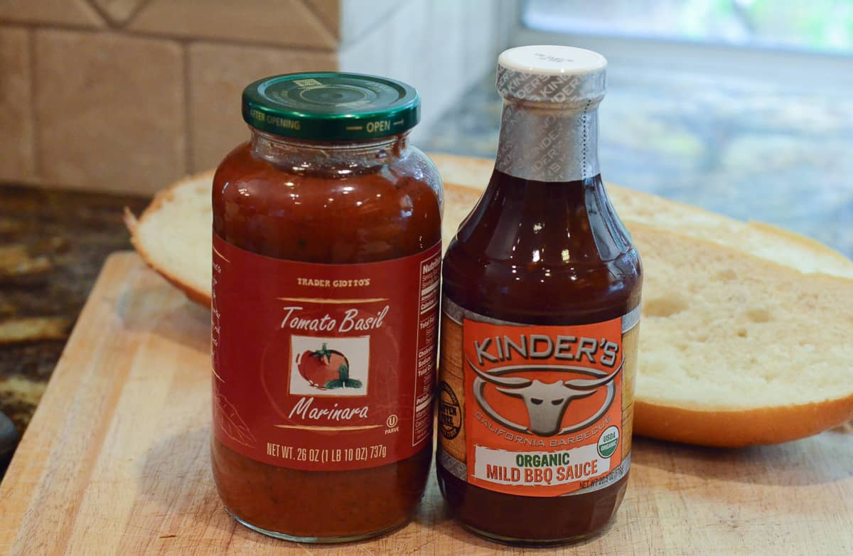 A jar of Trader Joe's Marinara and Kinder's BBQ Sauce on a kitchen counter.